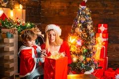 Junge Mutter mit Sankt-Hut und der kleine Junge schauen innerhalb des Kastens mit Weihnachtslicht Vektorversion in meinem Portefe stockfoto