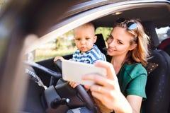 Junge Mutter mit Smartphone und Baby im Auto Lizenzfreies Stockbild