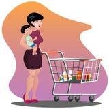 Junge Mutter mit Sohnbabykleinkind in einem Riemen, der voll Supermarktwarenkorb von Lebensmittelgeschäften drückt Stockfoto