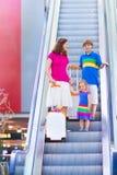 Junge Mutter mit zwei Kindern am Flughafen Lizenzfreies Stockbild