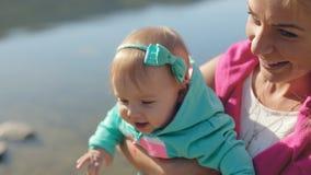 Junge Mutter mit zwei netten Töchtern nahe einem Teich stock video footage