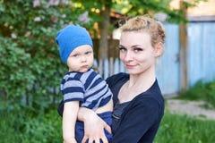 Junge Mutter umarmt ihren kleinen ernsten Sohn in einem Hut in der Natur stockbilder