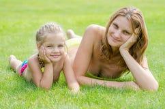 Junge Mutter und alte Fünfjahrestochter, die auf grünem Gras liegt und zum Rahmen schaut Lizenzfreies Stockfoto