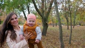 Junge Mutter und Baby haben den Spaß, der im Herbst am Park, die glückliche Familie im Freien ist, die Natur genießt stock video footage