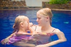 Junge Mutter und entzückende Tochter, die Spaß im Pool hat Lizenzfreies Stockfoto