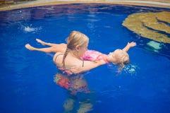 Junge Mutter und entzückende Tochter, die Spaß im Pool hat lernen Stockfotografie