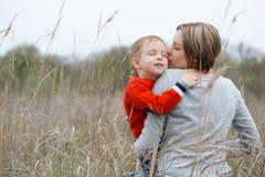 Junge Mutter und ihr kleiner Sohn umarmen sich ruhig und sensua Lizenzfreies Stockfoto