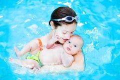 Junge Mutter und ihr kleines Baby in Schwimmen poo Stockfoto