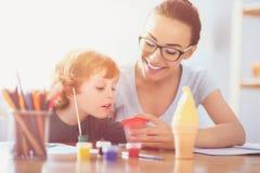 Junge Mutter und ihr Kleinkindsohn, die zusammen malt lizenzfreies stockfoto