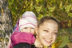 Junge Mutter und ihr Mädchen im Herbst Stockbilder