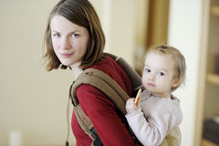 Junge Mutter und ihr Mädchen in einem Schätzchenträger Stockbilder