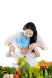 Junge Mutter und ihr Sohn, die einen Salat mischt Stockbild