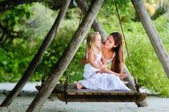 Junge Mutter und ihr wenig Tochterschwingen Stockfotografie