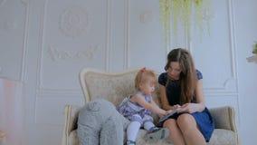 Junge Mutter und ihre Babytochter, die photobook schaut stock video