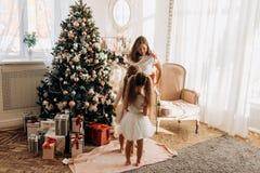 Junge Mutter und ihre bezaubernde Tochter zwei in den hübschen Kleidern stehen lizenzfreies stockbild