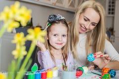 Junge Mutter und ihre schöne Tochter, die Ostereier malt Lizenzfreie Stockfotografie