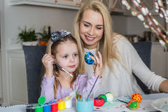 Junge Mutter und ihre schöne Tochter, die Ostereier malt Stockfoto