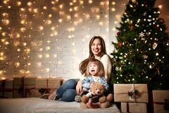 Junge Mutter und ihre Töchter nahe dem Weihnachtsbaum stockfoto