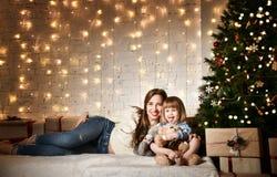 Junge Mutter und ihre Töchter nahe dem Weihnachtsbaum stockfotografie