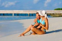 Junge Mutter und ihre Tochter auf tropischem Strand Stockbild
