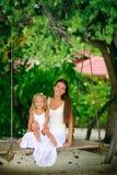 Junge Mutter und ihre Tochter, die an den Tropen schwingt Lizenzfreie Stockbilder