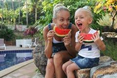 Junge Mutter und ihre Tochter, die Wassermelone isst Stockfotos