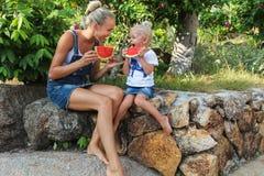 Junge Mutter und ihre Tochter, die Wassermelone isst Lizenzfreie Stockfotografie