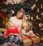 Junge Mutter und ihre zwei kleinen Töchter mit Weihnachtsgeschenken b Lizenzfreies Stockfoto