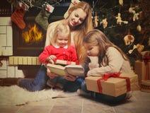 Junge Mutter und ihre zwei kleinen Töchter mit Weihnachtsgeschenken r Stockfotos
