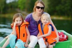 Junge Mutter und ihre zwei Töchter auf einem Boot Stockbilder