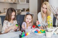Junge Mutter und ihre zwei Töchter, die Ostereier malen Stockbild