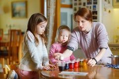 Junge Mutter und ihre zwei Töchter, die Ostereier malen stockbilder