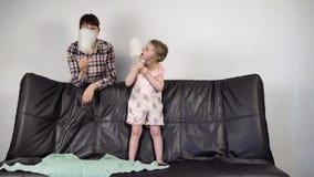 Junge Mutter und kleine süße Tochter essen zusammen Zuckerwatte zu Hause stock video footage