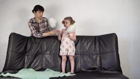 Junge Mutter und kleine süße Tochter essen zusammen Zuckerwatte zu Hause stock video