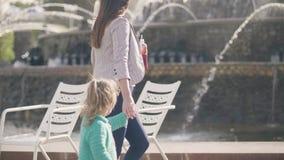 Junge Mutter und kleine Tochter, die auf Wasserbrunnenhintergrund im Sommerpark geht stock footage