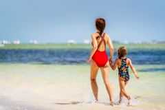 Junge Mutter und kleine Tochter, die den Strand in der Dominikanischen Republik genie?t lizenzfreie stockfotos