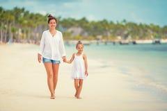 Junge Mutter und kleine Tochter, die den Strand in der Dominikanischen Republik genie?t stockbild