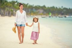 Junge Mutter und kleine Tochter, die den Strand in der Dominikanischen Republik genie?t lizenzfreies stockbild