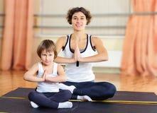 Junge Mutter und kleine Tochter, die in der Turnhalle trainiert Stockfotografie