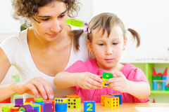 Junge Mutter und kleine Tochter, die mit Bauklötzen spielt Lizenzfreies Stockfoto