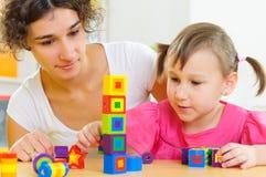 Junge Mutter und kleine Tochter, die mit Spielzeugblöcken spielt Stockfotografie
