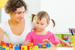 Junge Mutter und kleine Tochter, die mit Spielzeugblöcken spielt Lizenzfreie Stockfotos