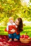 Junge Mutter und kleiner Sohn im Herbst mit einem Korb von Äpfeln Lizenzfreie Stockfotografie