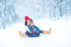 Junge Mutter- und Kleinkindtochter, die Schlitten genießt Stockfoto