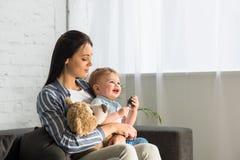 junge Mutter und lächeln wenig Baby mit dem Teddybären, der auf Sofa sitzt lizenzfreies stockfoto