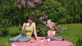 Junge Mutter und litlle Tochter auf einem Frühling picknicken nahe bei einer blühenden Flieder stock footage
