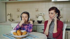 Junge Mutter und nette Tochter, die morgens in der Küche zu Hause frühstückt Hörende Musik des kleinen Mädchens mit stock video