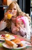 Junge Mutter- und Schätzchentochter, die frühstückt Stockfotografie