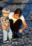 Junge Mutter und Sohn, die auf dem Strand am Sonnenuntergang spielt Lizenzfreie Stockbilder
