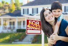 Junge Mutter und Sohn vor verkauft für Verkaufs-Real Estate-Zeichen lizenzfreies stockfoto